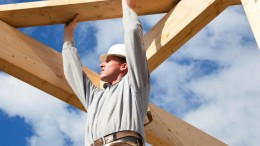 man-lifting-wooden-beams-against-blue-sky