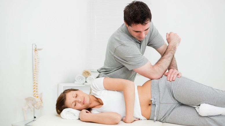Doctor using his elbow to massage the hip of a woman