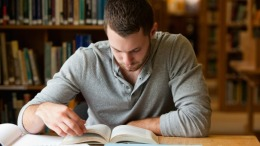 Male student researching with a book in a library