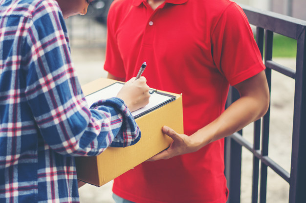 young-man-delivering-package-to-customer-at-home-delivery_1150-2963