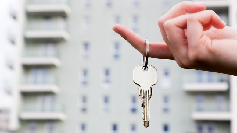 A real estate agent holding keys to a new apartment in her hands