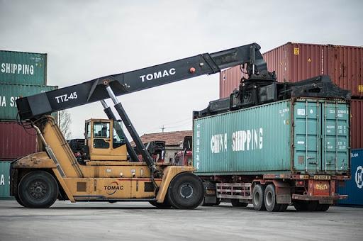 Hydrauliczny dźwig samochodowy transportujący kontener w porcie